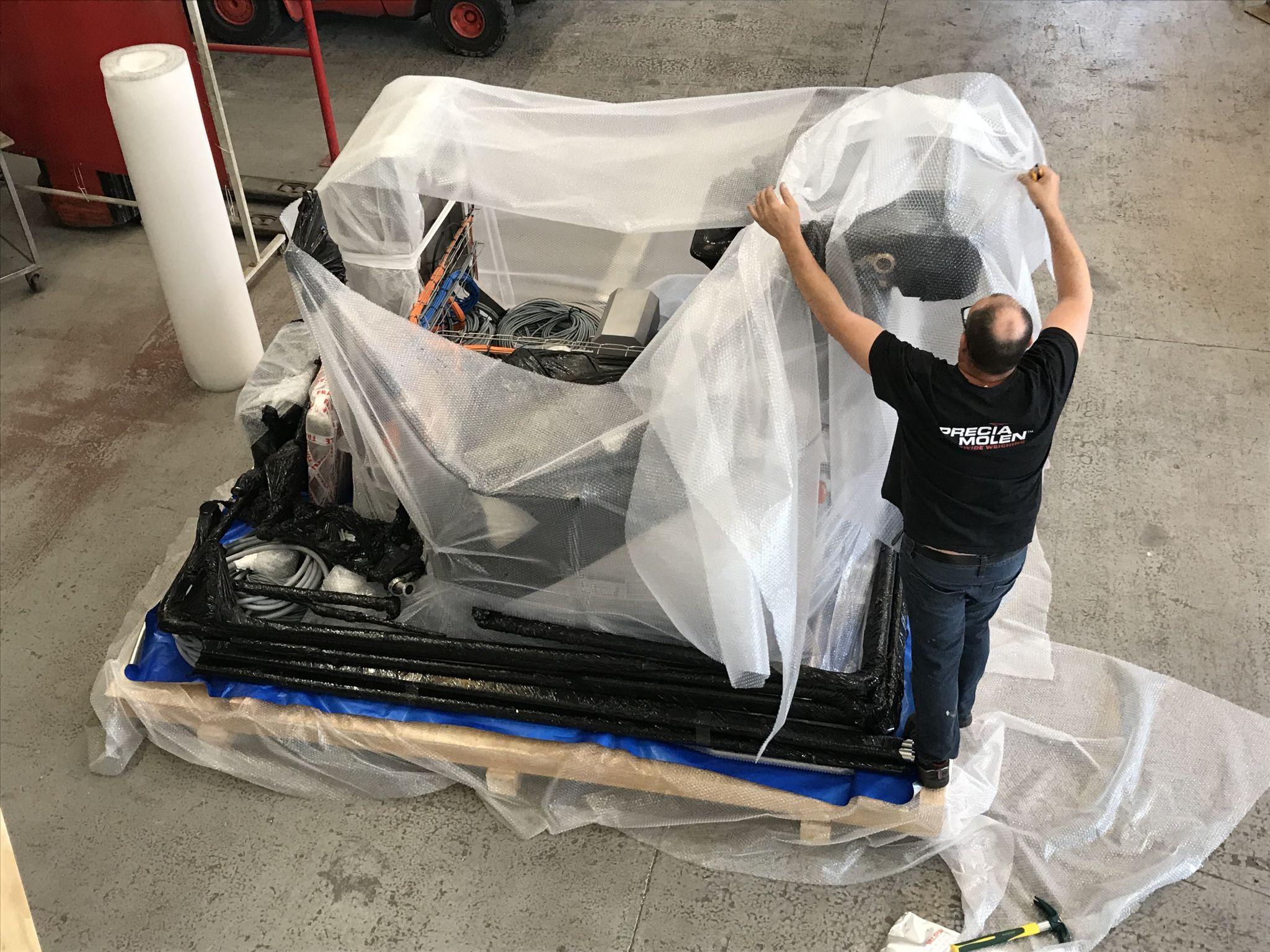 Emballage du SKID par des professionnels avant l'expédition par bateau